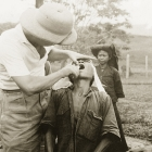 A man receives dental treatment from a British medical officer at Keningau Health Centre. Keningau, North Borneo (Sabah, Malaysia), circa 1937