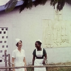 A European nurse and an African midwife share a joke outside the children's ward of a Church of Nigeria hospital. Nigeria, circa 1970