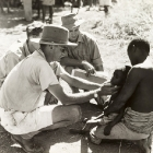 A European medic, identified as Dr Cookson, is assisted by two others as he examines a young child suffering from sleeping sickness (African trypanosomiasis). Probably Northern Rhodesia (Zambia), circa 1950