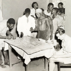 A group of African men queue at a dispensary, where two African medics are taking blood samples. A European doctor sits writing notes next to a table, on which the blood samples are laid out on slides. Probably Northern Rhodesia (Zambia), circa 1950