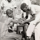 An African medic gives an injection to a female patient, while a European doctor stands by a medical trolley and observes. Probably Northern Rhodesia (Zambia), circa 1950